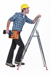 Carpenter with drill climbing step-ladder