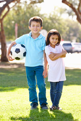 Two Children Playing Soccer Together