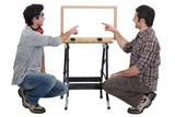 Father and son making wooden frame
