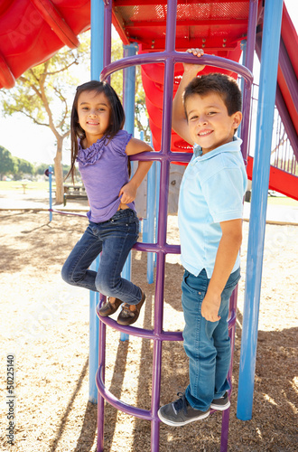 Boy And Girl On Climbing Frame In Park