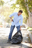 Man Picking Up Litter In Suburban Street