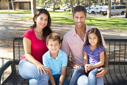 Family Sitting On Park Bench Together