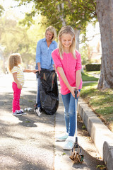 Mother And Daughters Picking Up Litter In Suburban Street