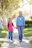 Mother And Daughter Walking To School On Suburban Street