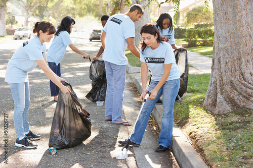 Team Of Volunteers Picking Up Litter In Suburban Street