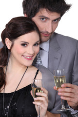 Young man and woman smiling holding champagne glasses
