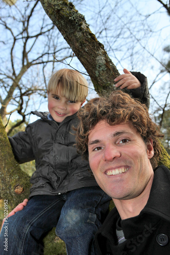 Little boy climbing tree with father