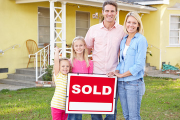 Family Standing By Sold Sign Outside Home