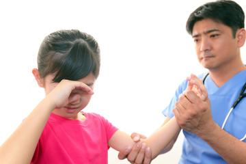 痛みを訴える患児と医師