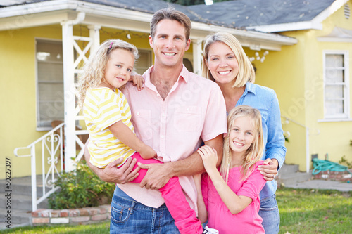 Family Standing Outside Suburban Home