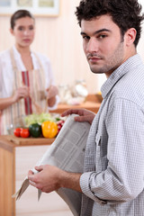 young woman cooking and boyfriend reading newspaper