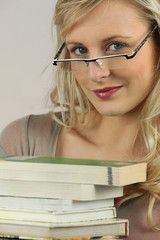 Blonde woman with glasses and stack of books