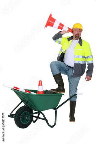 Worker listening through a traffic cone