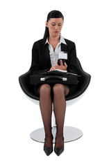Businesswoman sat in chair with briefcase and mobile
