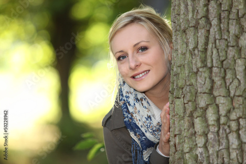 blonde outdoors with hands resting on bole