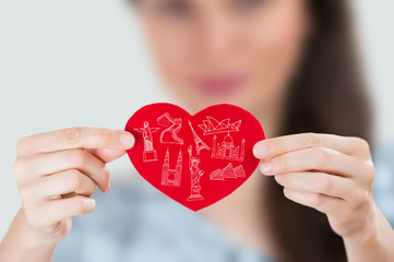 Female holding heart with her arms and famous touristic symbols