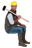 Man with sledge-hammer sat on stool