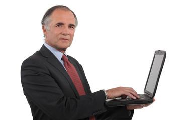 A mature businessman with a laptop.