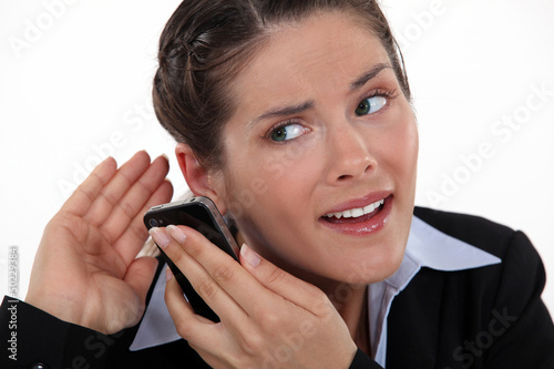 young businesswoman straining her ears with cell phone