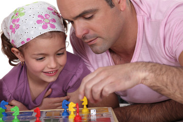 Father and daughter playing board game