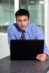 Young businessman using laptop computer