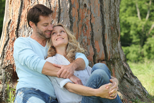 Happy couple sat by tree