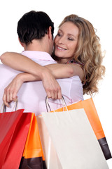 Woman with bags hugging boyfriend
