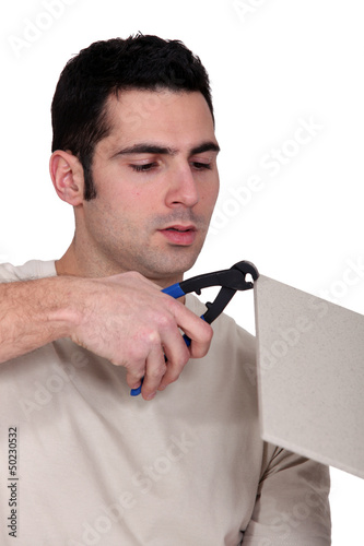 Man clipping a tile