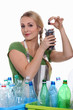 Woman recycling batteries and plastic bottles