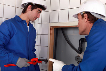 Plumber and his apprentice working together