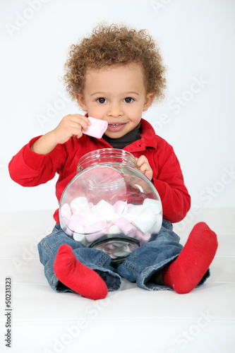 Toddler eating marshmallows