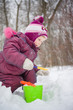 Adorable girl dig snow with small shovel and pail in park
