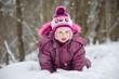 Adorable girl crawl in deep snow in park