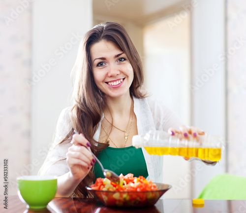 Woman pouring vegetable oil  salad