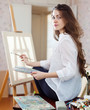 Long-haired woman with oil colors near easel