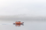 Smale lone orange boat sailing in mist