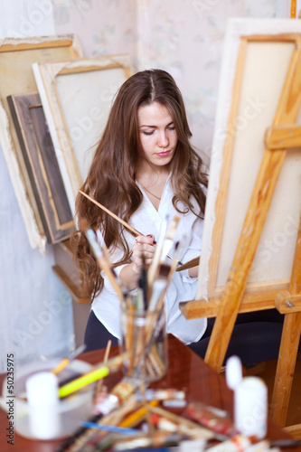 Long-haired  artist paints on canvas