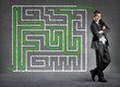 Businessman solved a maze on a wall