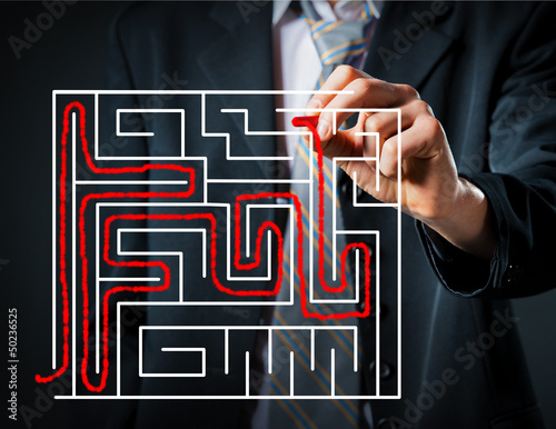 Businessman solving a maze close up