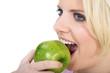 Junge blonde Frau beisst in grünen Apfel