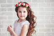 Portrait of a beautiful little girl in a wreath