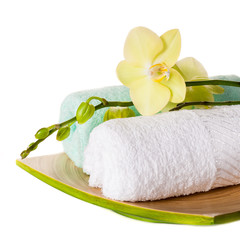 Spa concept: orchid and towels on white background