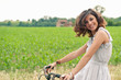 Beautiful smiling young woman portrait with bike in the country