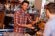 Bartender serving draught beer in bar