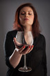 Woman with glass of red wine in her hand on grey background.