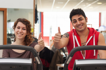 Young couple training in the gym with bike.