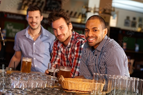 Young men drinking beer at bar counter
