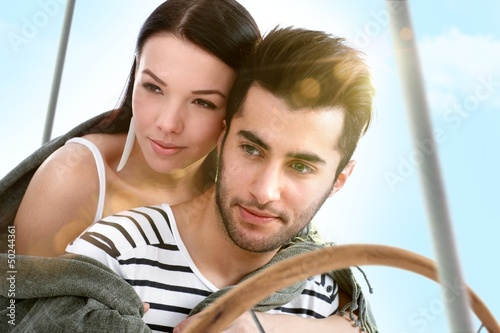 Loving couple embracing on sailing boat at summer