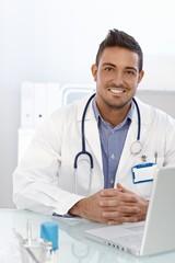 Happy doctor sitting at desk