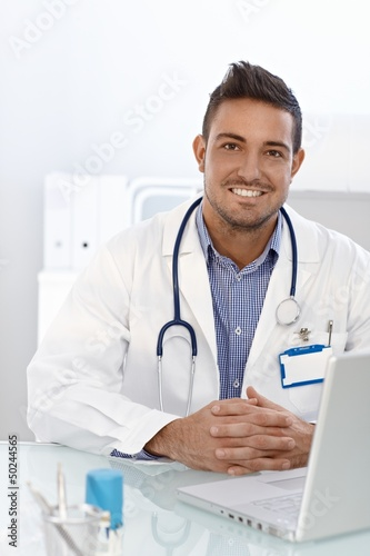 Happy doctor sitting at desk